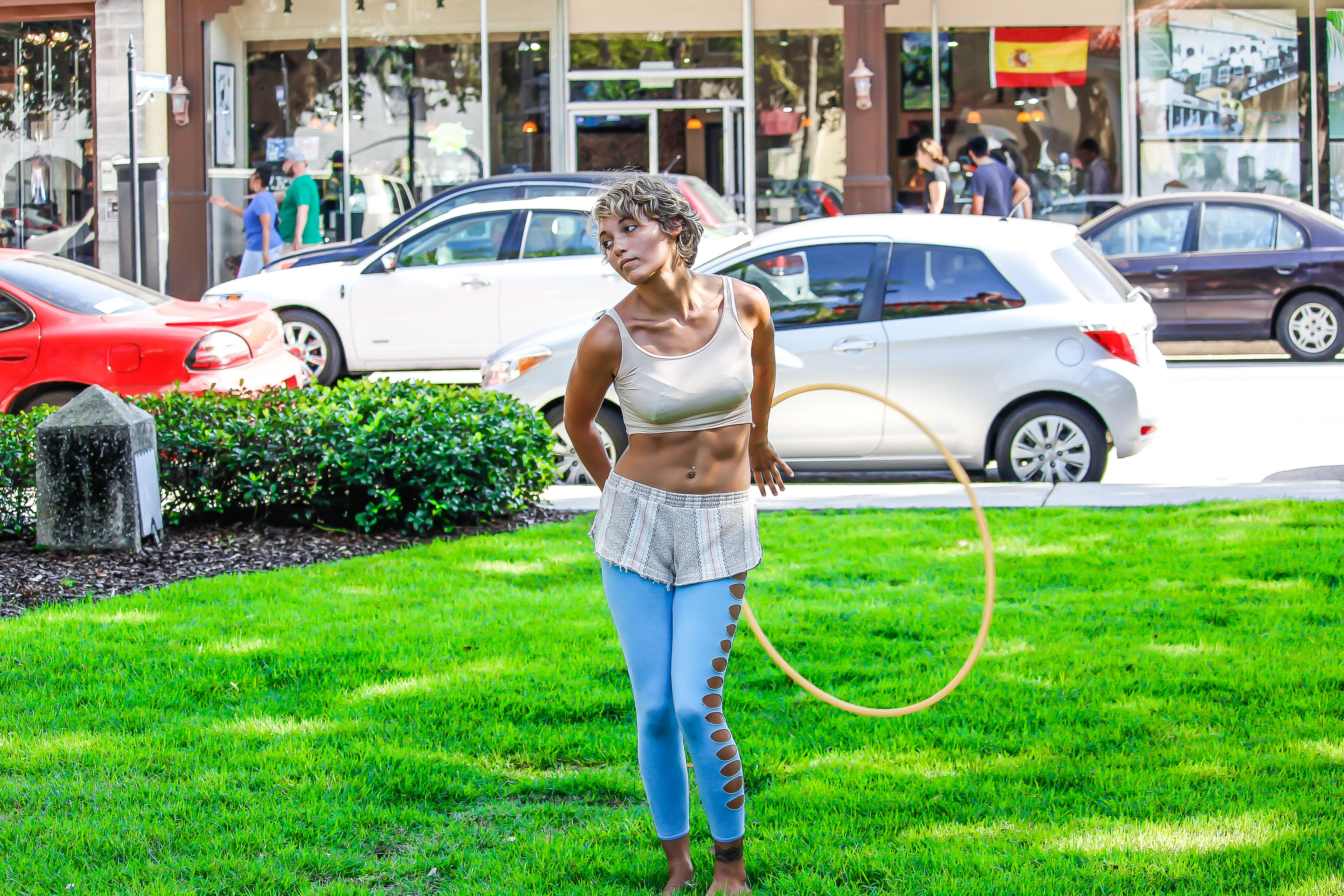 Woman in White Sleeveless Shirt and Blue Pants Holds Yellow Hula Hoop Stands on Green Grass