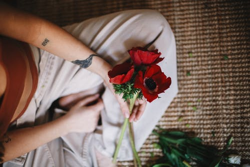 From above of crop anonymous person in casual clothes sitting with bouquet of red poppy flowers on carpet