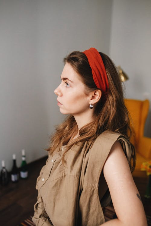 Side view of emotionless female with long brown hair looking away in blurred room