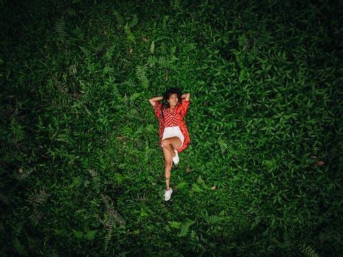 Mulher De Camiseta Vermelha E Short Branco Correndo No Campo De Grama Verde