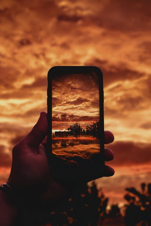 Close-Up Photo of Person Taking Photo of Sunset