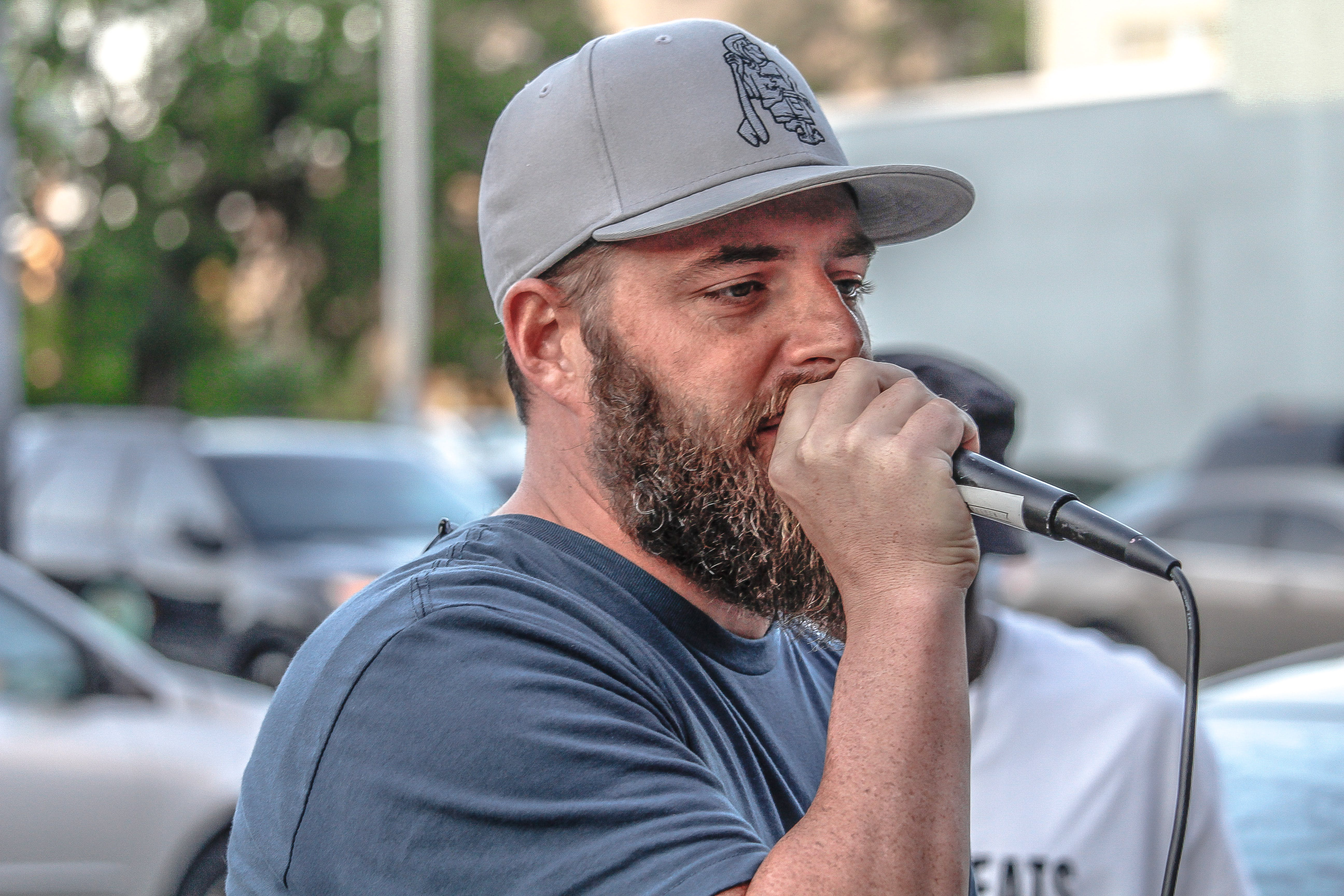 Man In Crew-neck Shirt And Grey Cap Holding Black Corded Microphone