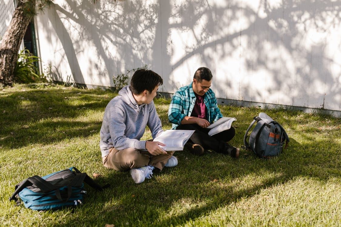 College Students Sitting on the Grass while Reading Books