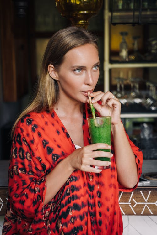 Woman in Red and White Polka Dot Shirt Drinking from Green Glass Cup