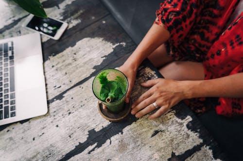持有與綠色液體的綠色水杯的人