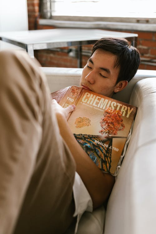 A Man Sleeping on the Sofa While Holding a Chemistry Book