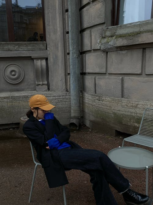 Side view of unrecognizable young female in stylish clothes and orange cap sitting on chair near building on street