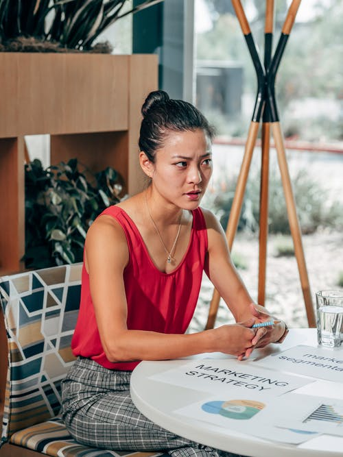Serious Asian marketer speaking at desk with papers in office