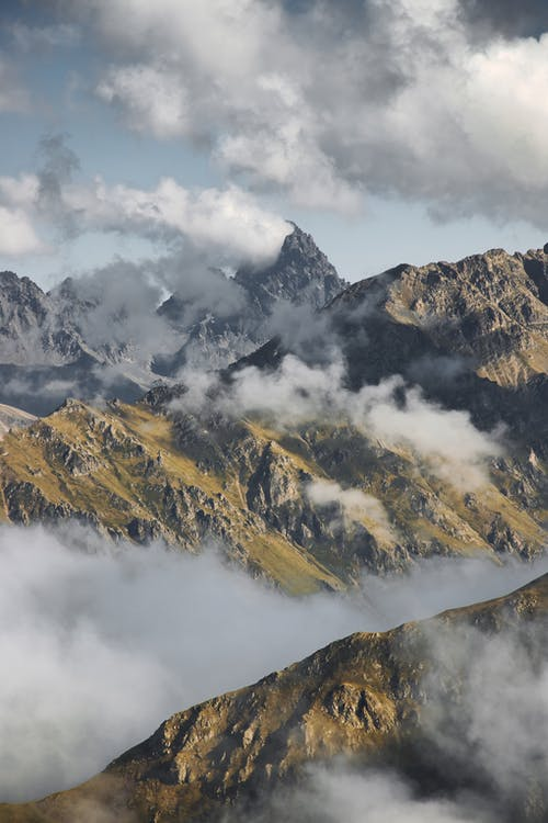 Sharp peaks of rocky mountains under cloudy sky