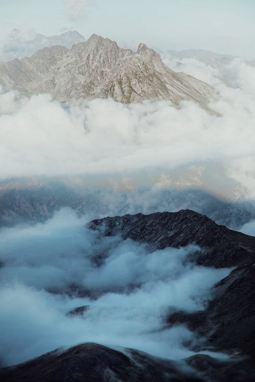 White fluffy clouds floating over massive rocky mountains located in volcanic terrain in sunlight