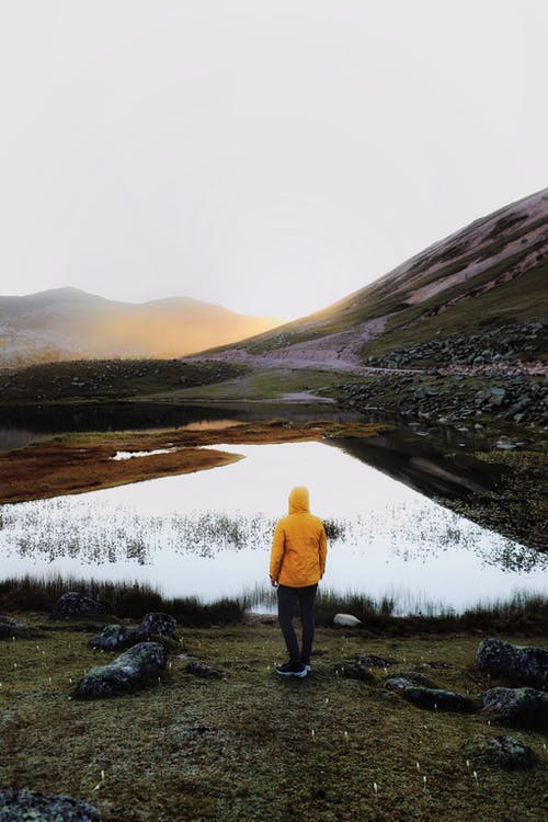 Back view of anonymous hiker in warm hooded yellow jacket standing near calm river with mirrored surface flowing through mountainous valley and reflecting sky at sunset