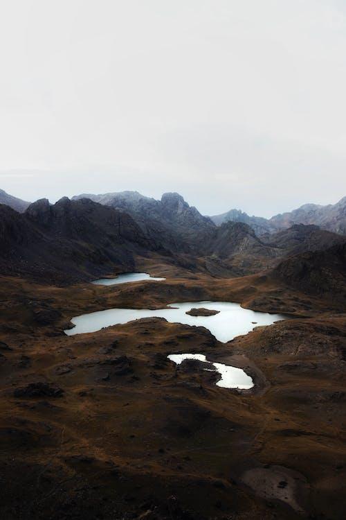 Mountainous landscape with calm lakes against misty sky