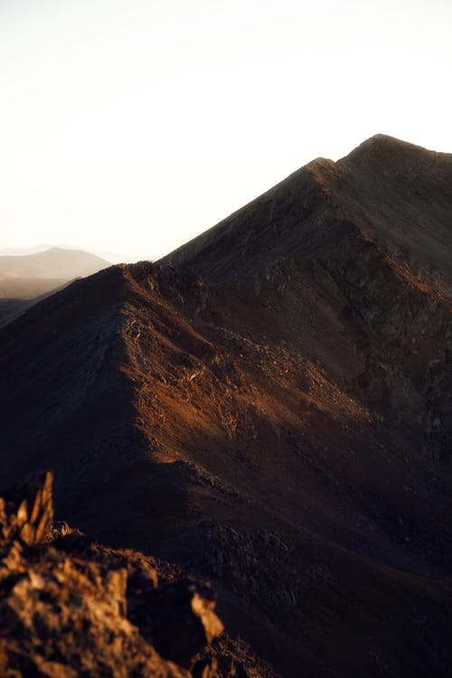 Picturesque scenery of steep slopes of powerful massive rocky mountains against sunset sky in highland