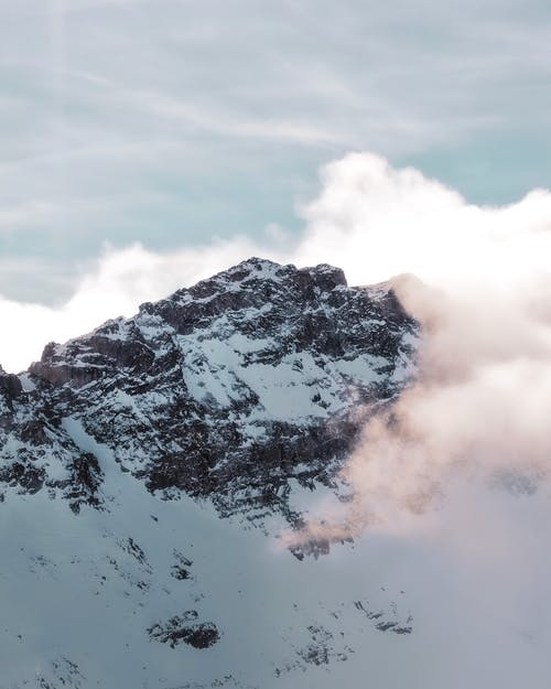 Scenery of snowy mountain ridge covered with snow and clouds in steep rocky terrain
