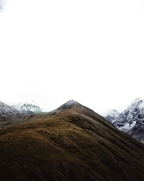 Hill among steep snowy mountains in highland