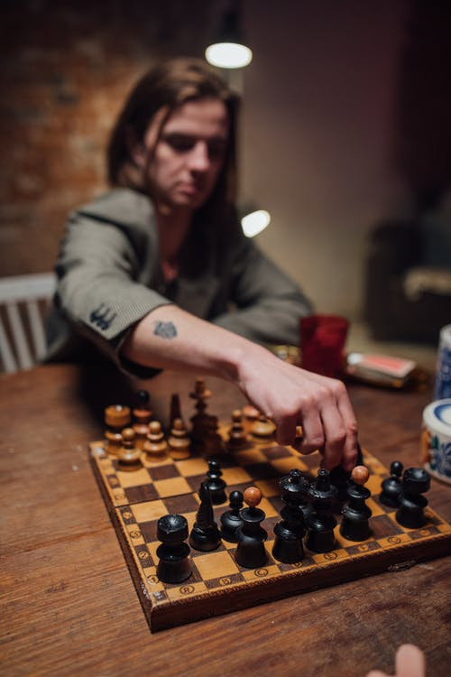 Man Playing Chess Game on Brown Wooden Table