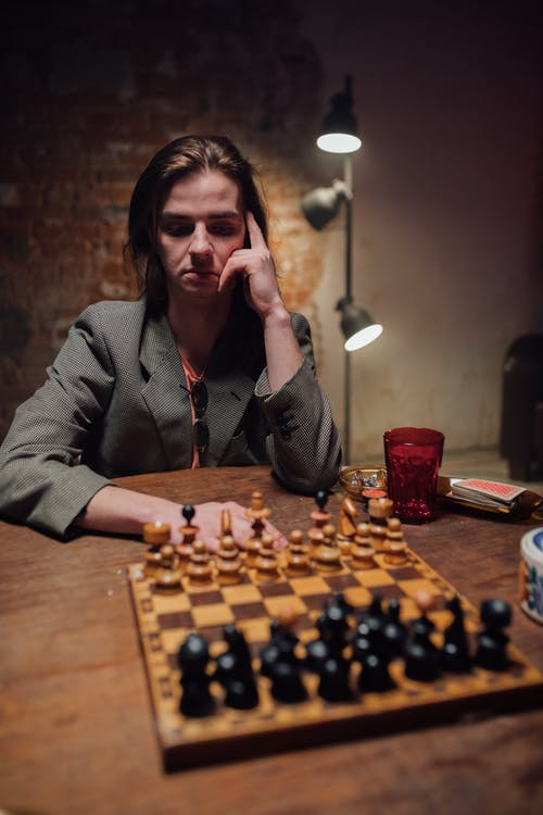 Woman in Gray Coat Sitting Beside Brown Wooden Table With Chess Pieces