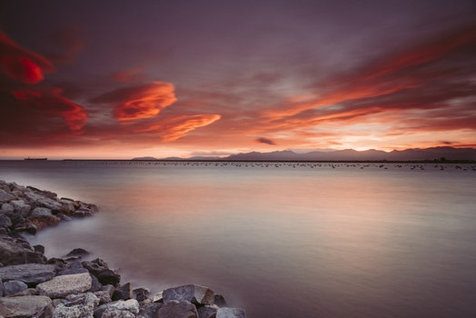 Landscape Photography of Rocks Near Body of Water during Sunset
