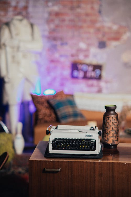 Black and White Typewriter on Brown Wooden Table
