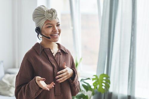 Smiling black operator in headset speaking