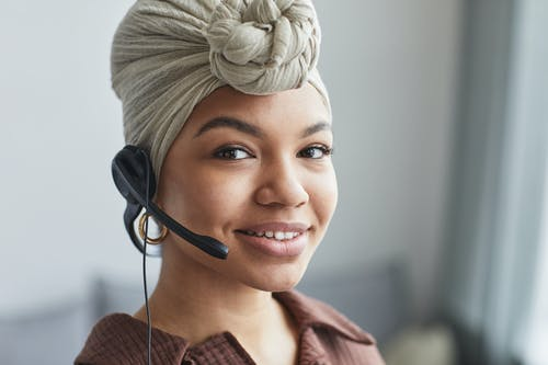 Delighted African American female call agent with headset wearing turban looking away while standing in light room on blurred background