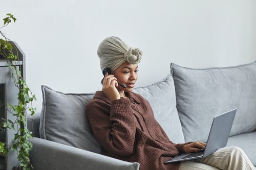Black woman with headset browsing laptop