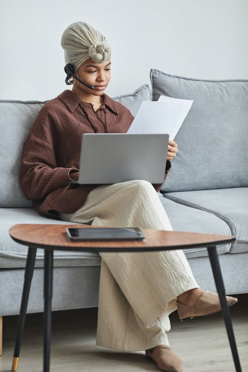Woman in Red Sweater Sitting on Gray Couch Using Macbook