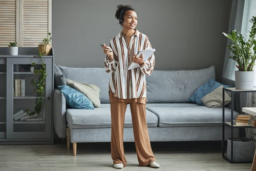 Woman in White and Brown Robe Standing on Gray Couch