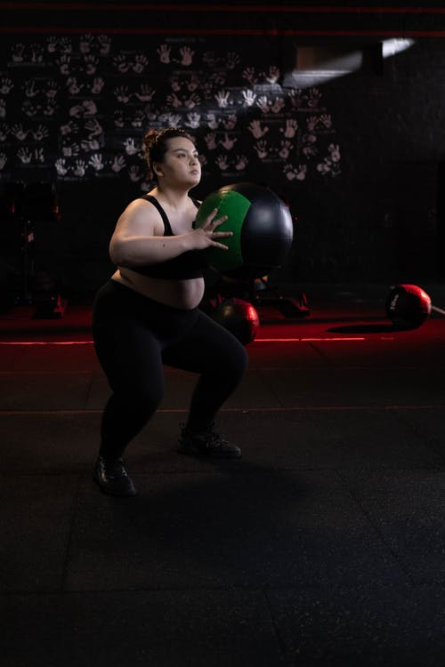Woman in White Sports Bra and Black Leggings Holding Green Ball