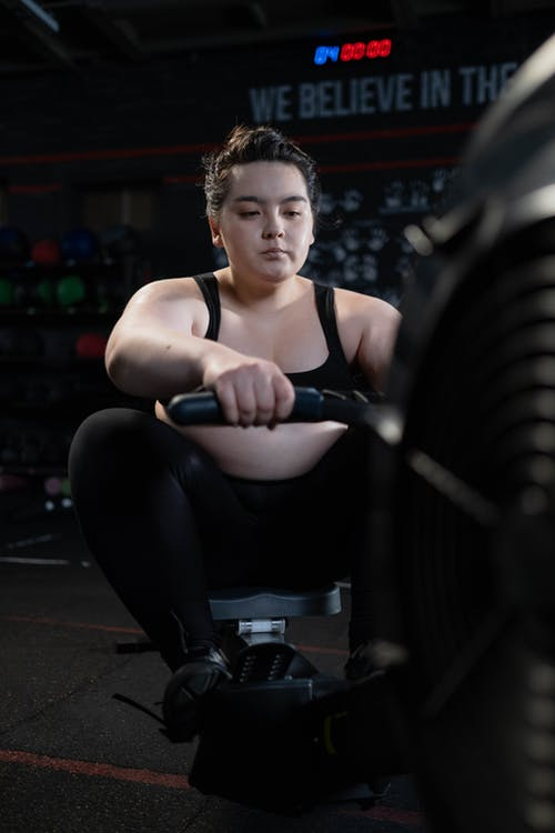 Woman in Black Sports Bra and Black Leggings Exercising