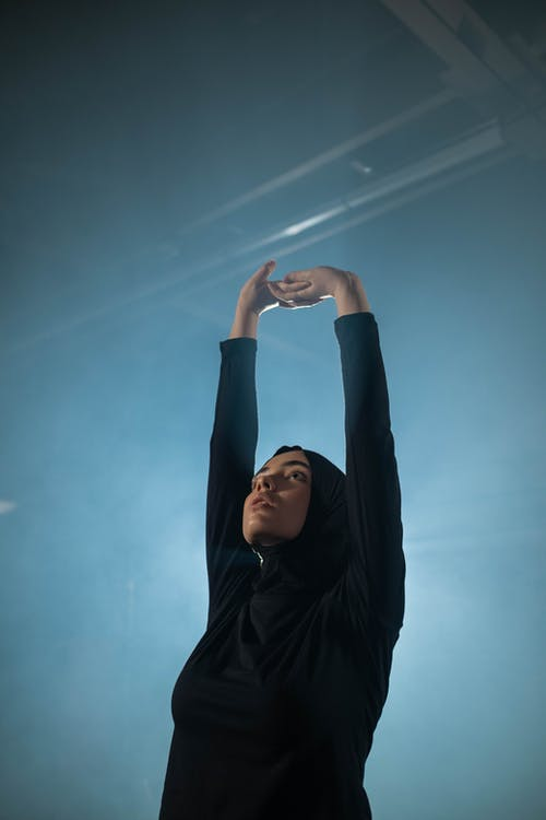 Woman in Black Long Sleeve Shirt Raising Her Hands