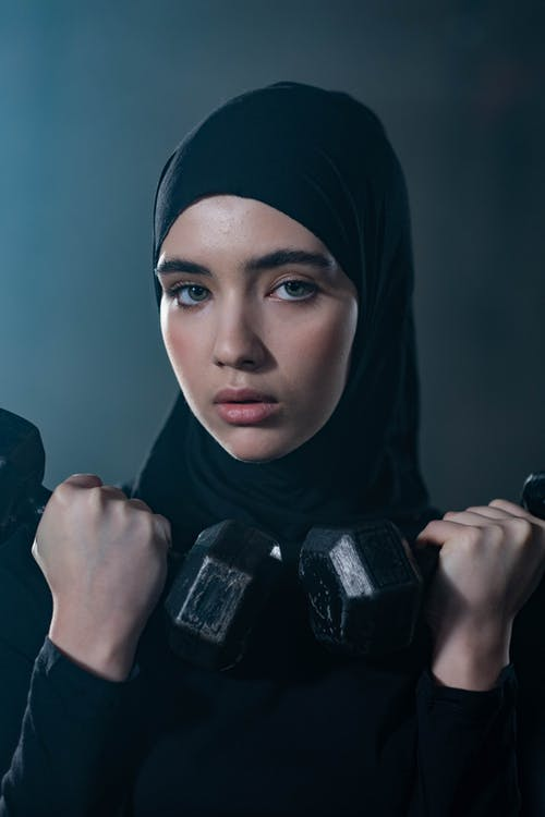 Woman in Black Hijab Holding 2 Black Dumbbells