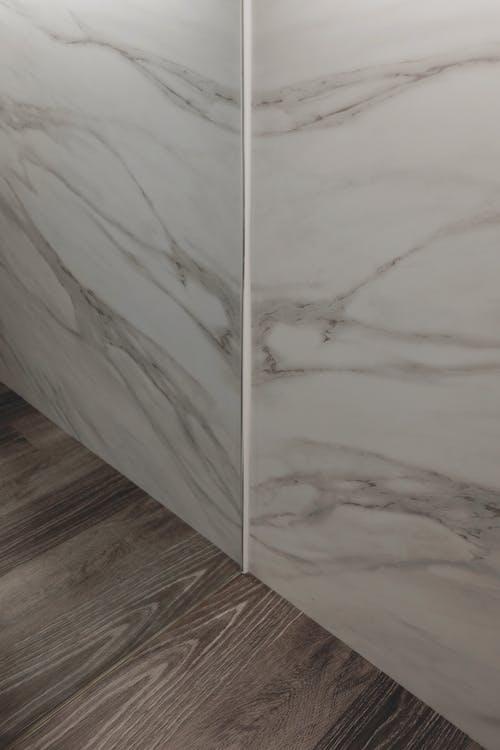 White Textile on Brown Wooden Parquet Floor