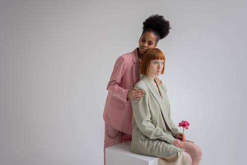 Delicate African American female in pink suit hugging serious red haired woman sitting with blooming flower against gray background