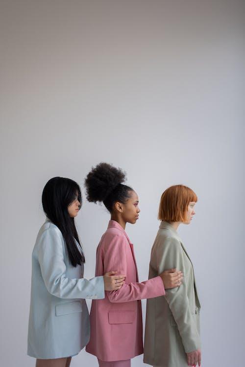 Multiracial women in stylish blazers in studio