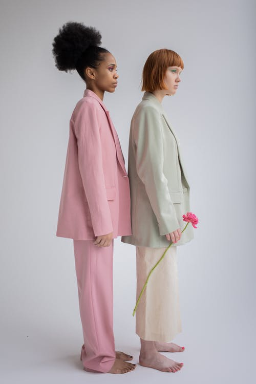Full body side view of multiethnic female models wearing trendy oversize clothes standing close against gray background
