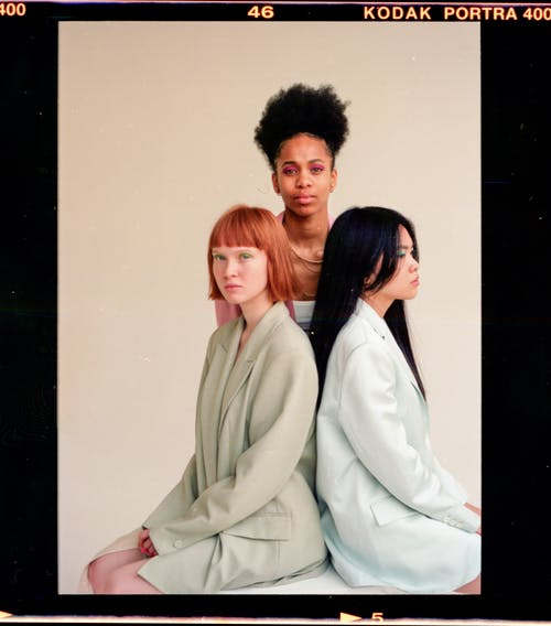 Emotionless diverse female models wearing stylish blazers sitting on cube against black woman on gray background
