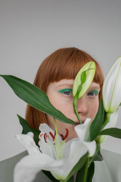 Shy woman hiding behind blooming flowers
