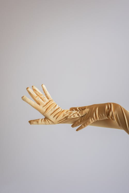 Crop anonymous female gently touching hands in silk vintage gloves in studio against gray background