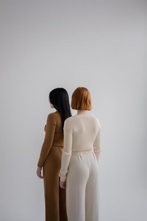 Back view of unrecognizable female models wearing pants and sweaters standing together against gray background in studio