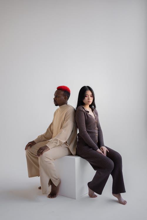 Multiracial unemotional man and woman sitting on cube