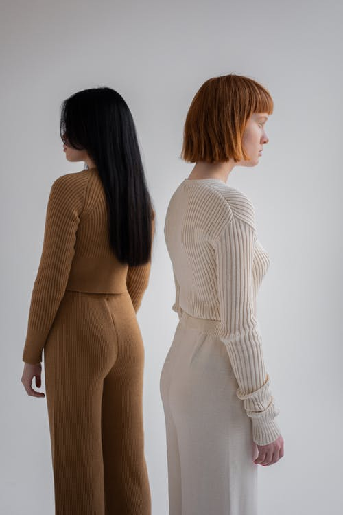 Back view of unrecognizable female models in light outfits looking away while standing on white background in studio