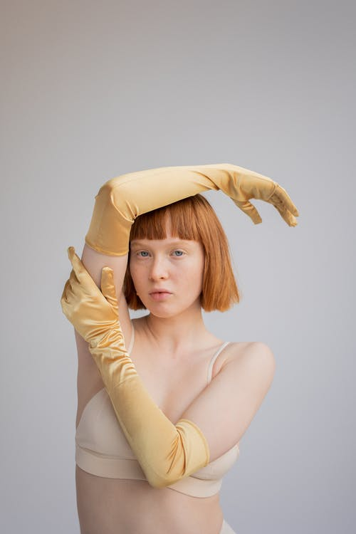 Confident woman in bra and gloves