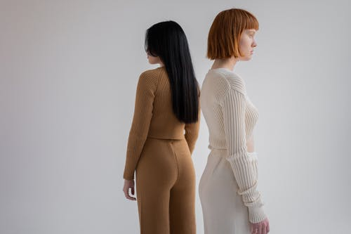 Back view of unrecognizable young female models wearing cozy simple suits while looking away and standing on white background in studio
