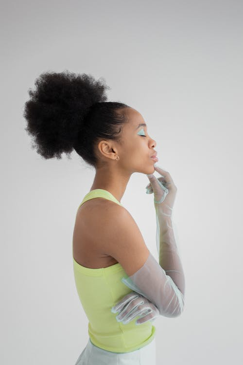Black woman in gloves touching chin with finger