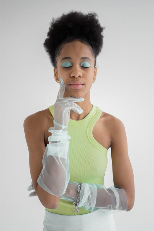 Pensive African American female with curly hair and makeup of blue eyeshadows wearing light green shirt without sleeves and transparent gloves of organza touching face with finger