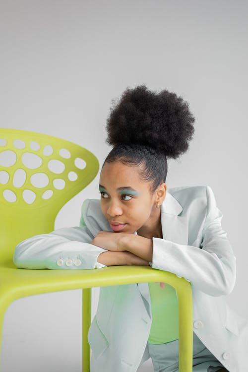 Thoughtful African American female with vivid makeup sitting on floor and leaning chin on crossed hands on neon yellow modern chair and looking away