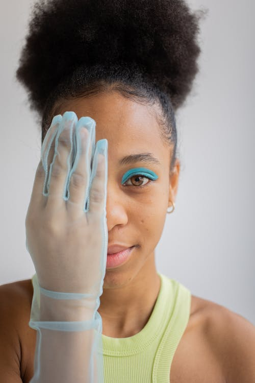 Black woman with artistic makeup closing one half of face
