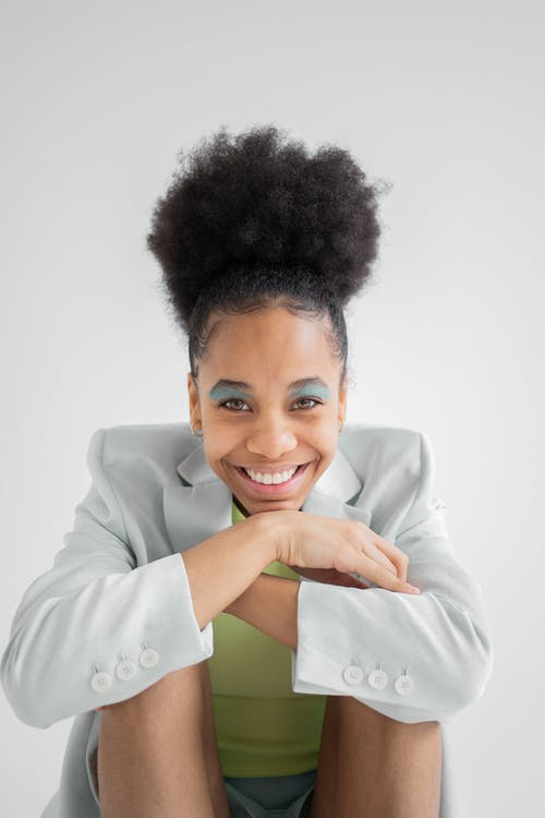 Smiling African American female model with curly hair and trendy visage sitting with bent legs and crossed arms
