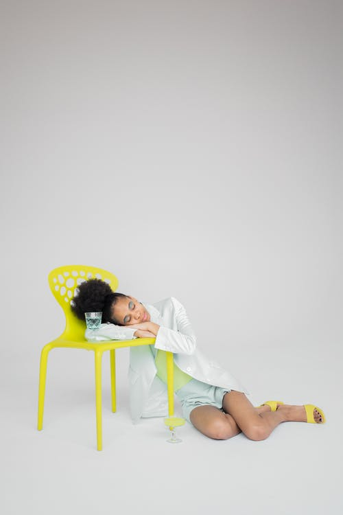 Black woman putting head on bright neon yellow chair